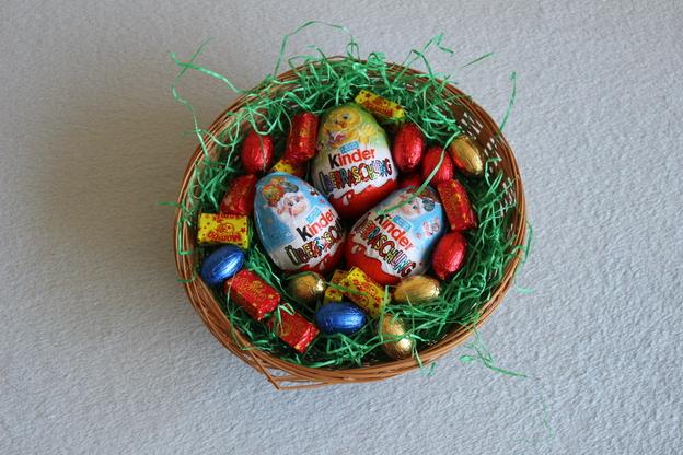 Legen Sie Eier und Süßigkeiten in den Korb.