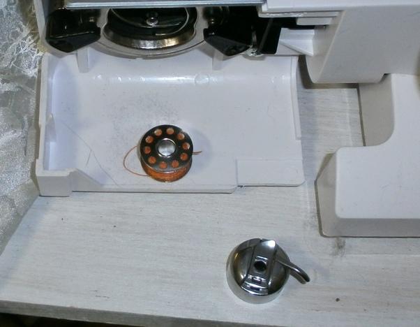 Spulen Sie Garn in einer anderen Farbe auf die Unterfadenspule.