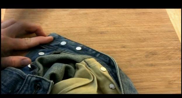 Legen Sie die Hose mit dem Knopfoberteil auf den Tisch.