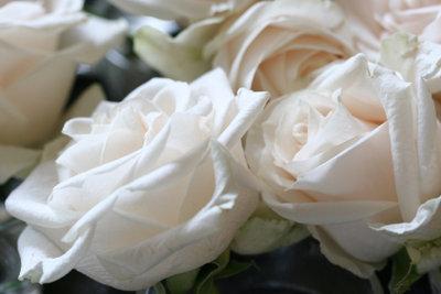 Edle Blumengestecke verschönern den Hochzeitstisch.