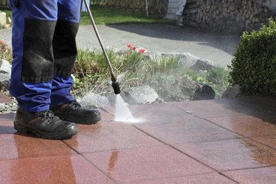 Mit dem Wasserstrahl werden Steinplatten sauber.