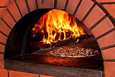 Im Steinbackofen brennt ein echtes Feuer.