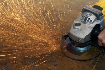 Mit einer Schleifmaschine alten Kleber entfernen.