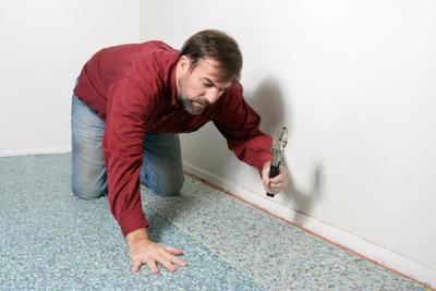 Reparatur eines Brandlochs im Teppich.