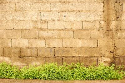 Bauen Sie die Stützmauer aus Betonsteinen.