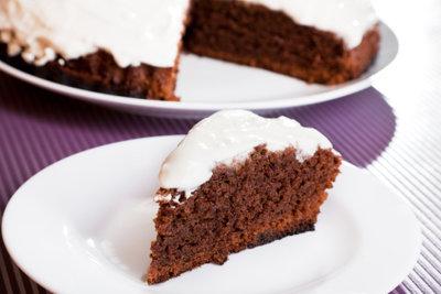 Weiße Sahnehauben zieren Schokoladenkuchen besonders schön.