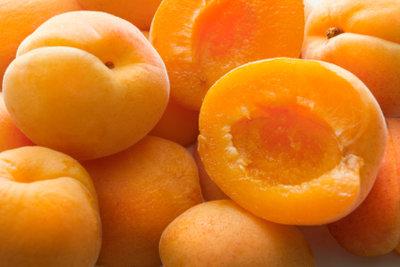 Entsteinen und halbieren Sie die Aprikosen.