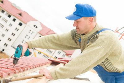 Dachdecker verlegen Dachschindeln professionell.