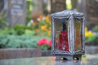 Das Grab mit stabilem Windlicht schmücken