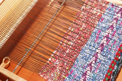 Ein farbenfroher Teppich aus Baumwolle entsteht.