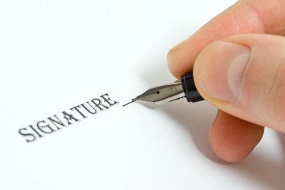 Schriftstücke am Comuter unterschreiben.