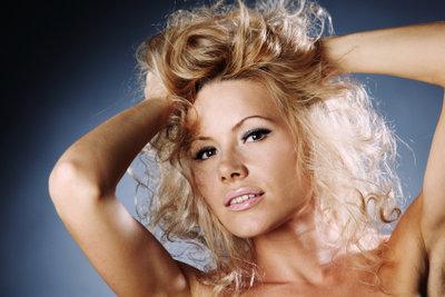 Cindy Lauper fällt mit blonden Locken auf.