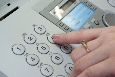 Beim öffentlichen Fax-Gerät hilft der Angestellte.