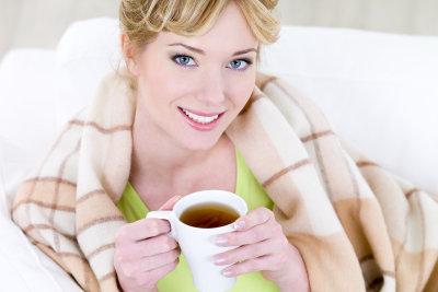 Warmer Tee und eine Decke helfen gegen Frieren.