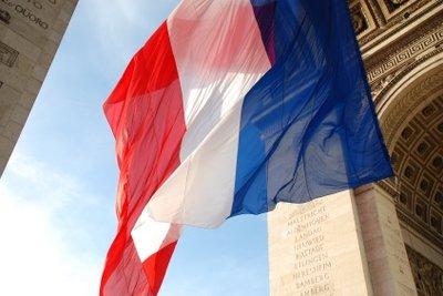 Die wehende Tricolore unter dem Arc de Triomphe in Paris.