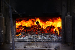 Ein Holzofen spendet angenehme Wärme und spart Heizkosten.