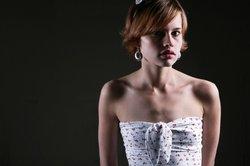 Make-up und Accesoires sorgen für ein weibliches Äußeres trotz kurzer Haare.