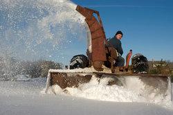 Eine Schneefräse wirft den Schnee in hohem Bogen aus.