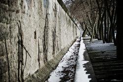 """""""Menschliche Erleichterungen"""" zeigt die Mauer mit Blümchentapete."""