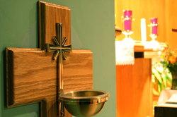 Katholiken bekreuzigen sich mit Weihwasser.