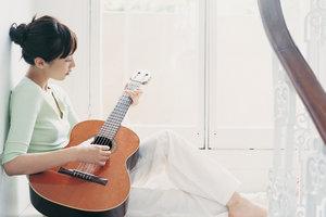 Schlagen Sie Ihre zarte Saite auf der Gitarre an.