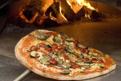 In der Pizzeria wird die Pizza sehr heiß gebacken.