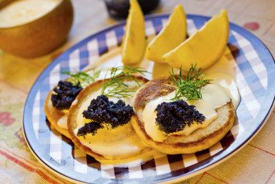 Servieren Sie die Blinis mit Kaviar.