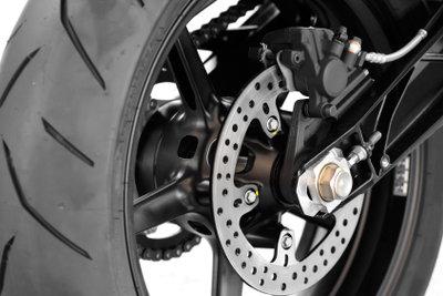 Hinterrad eines Motorrads mit Stellschraube und Kette.