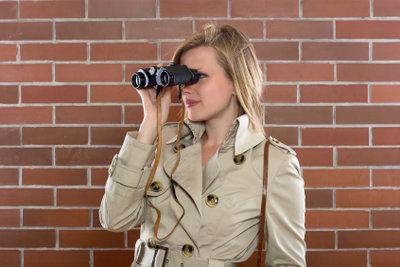 Werden Sie Spion - hier klassisch mit Trenchcoat und Fernglas.