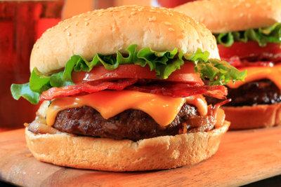 Für den selbst gemachten Hamburger müssen Sie Fleisch braten und ihn mit frischen Zutaten belegen.