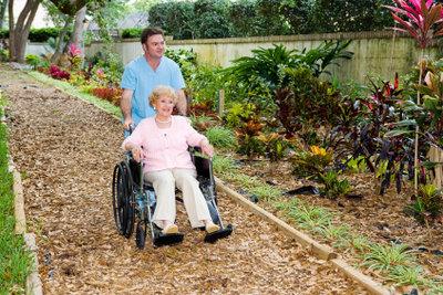 Eine Pflegehilfskraft unterstützt hilfsbedürftige Menschen.